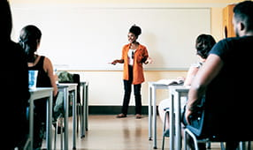 Female teacher in front of a classroom filled with parents